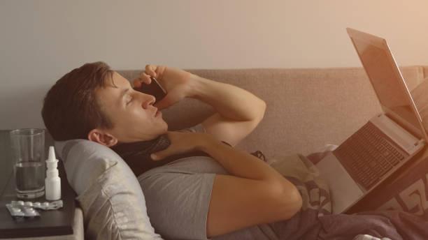 Kranken jungen Mann im Bett arbeiten am Notebook und am Telefon zu sprechen. Viele Pillen und Medikamente sind auf dem Nachttisch – Foto