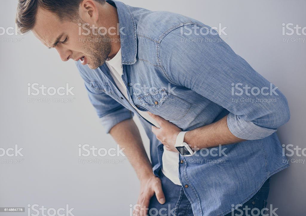 Sick young man leaning on the wall stock photo