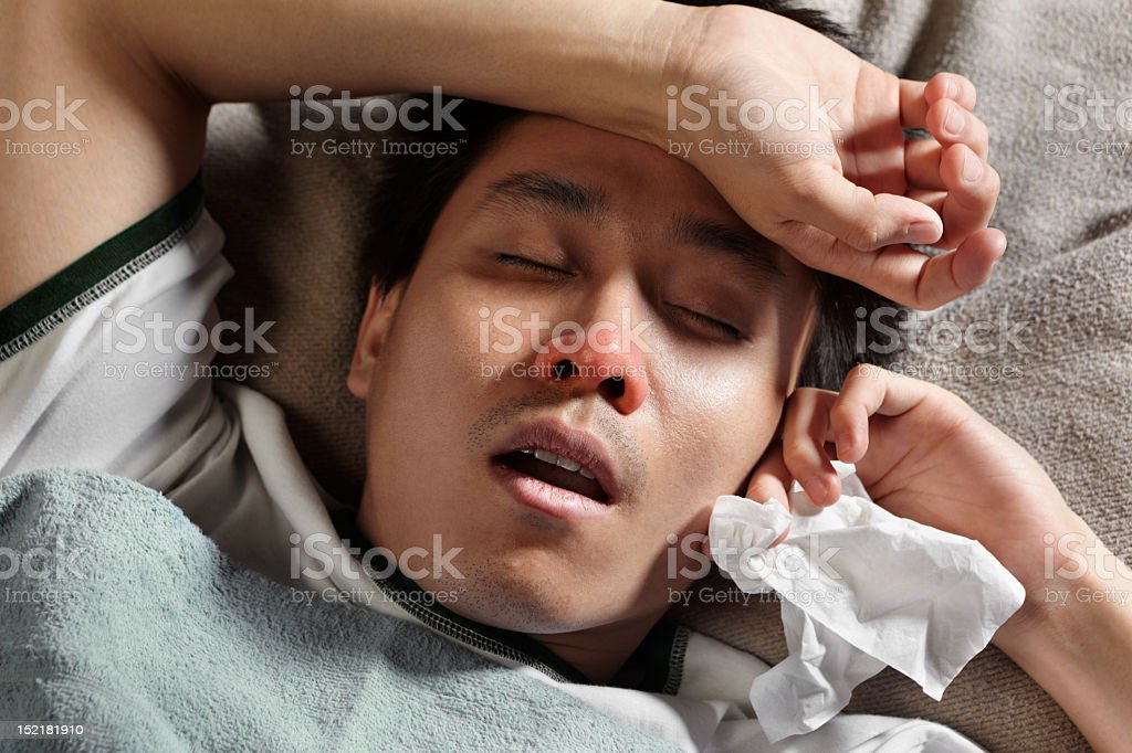 A sick young man lying down holding a tissue royalty-free stock photo