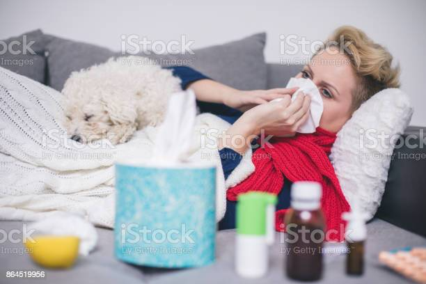 Sick young woman at home on the sofa with a cold she is covering with picture id864519956?b=1&k=6&m=864519956&s=612x612&h=2l7vu3f rpzpklusasaal8grdqc9iqgasvfflcgw yu=