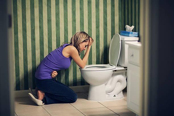 sick young woman at toilet - kotze stock-fotos und bilder