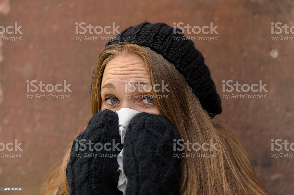 Sick Young Woman in Winter Attire Blowing her Bose stock photo