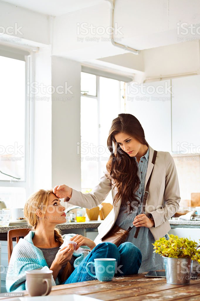 Sick young woman Young woman has a cold, sitting in a kitchen wrapped in blanket, her friend touching her forehead. 20-24 Years Stock Photo