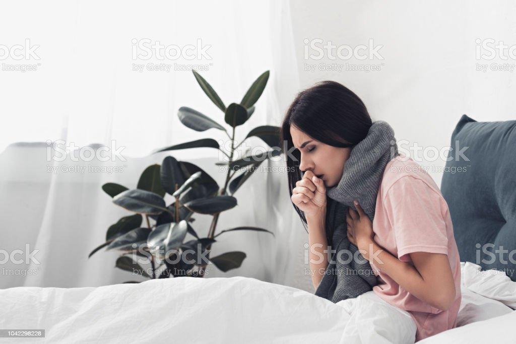 Kranke junge Frau im Bett sitzen und mit Husten und Halsschmerzen leiden – Foto