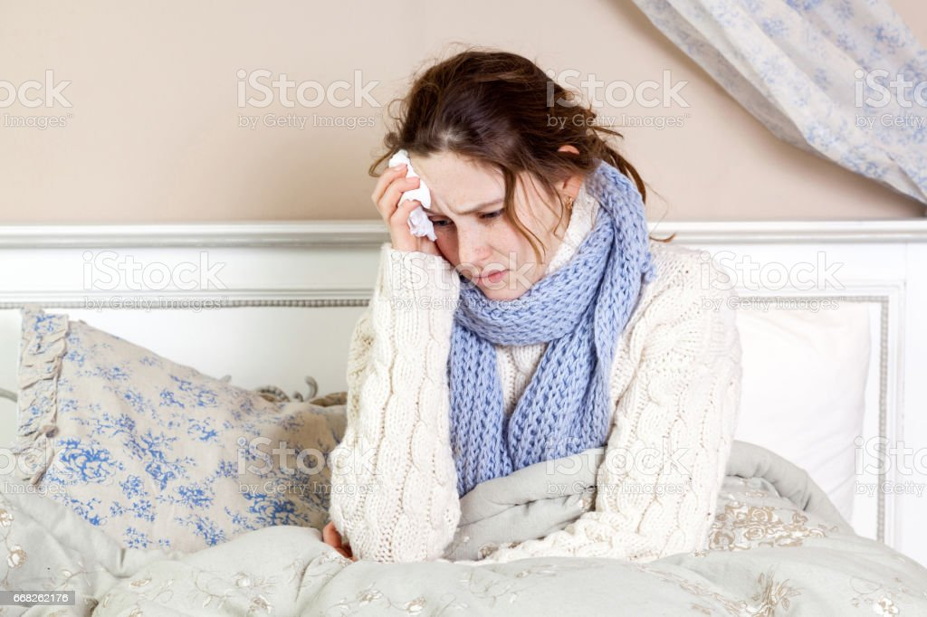 Sick young woman with blue scarf and suffering from terrible headache while lying in bed. foto stock royalty-free
