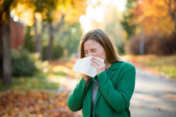 Sick young woman with cold and flu Sick young woman with cold and flu standing outdoors, sneezing, wiping nose with handkerchief, coughing. Autumn street background allergy stock pictures, royalty-free photos & images