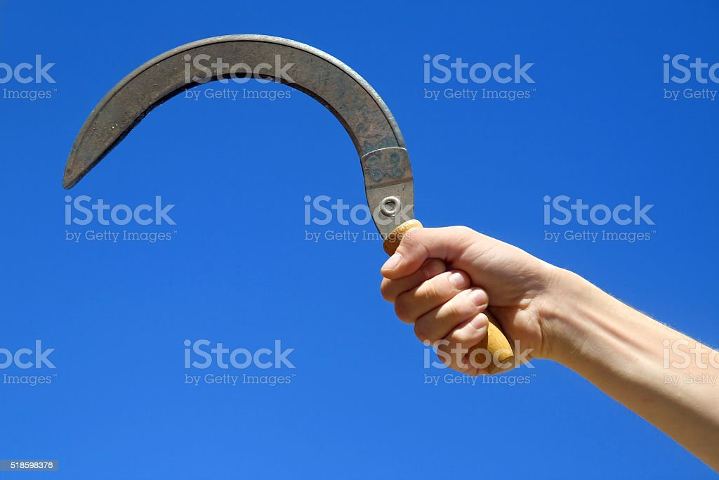 sickle in hand on blue background stock photo
