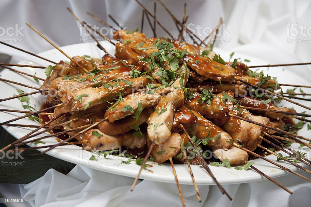 Side angle Teriyaki BBQ asian chicken skewers on white platter royalty-free stock photo