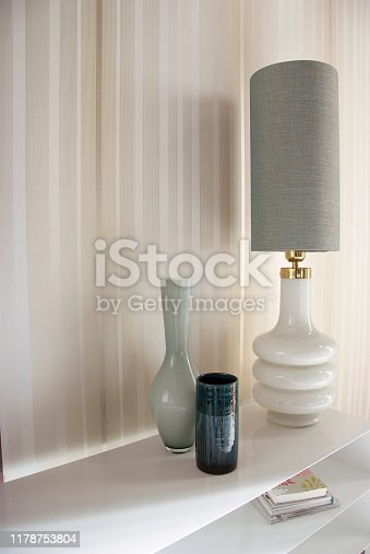 Shot of glass vase and electric lamp on side board