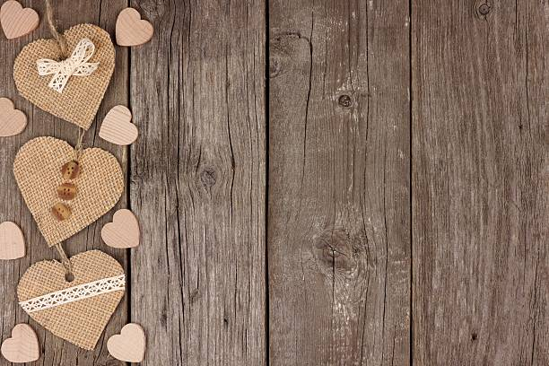 Side Border Of Handmade Burlap Heart Decorations Over Rustic Wood Stock Photo