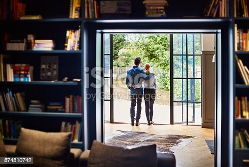 Rearview shot of a couple looking at the view outdoors from their home