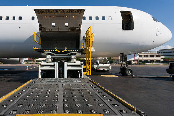 Side cargo hatch of plane open to receive cargo stock photo