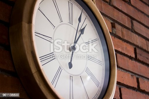 671883446istockphoto Side close–up of a wooden wall clock with roman numerals hanging in a red brick wall. 961138800