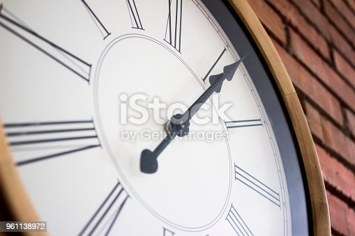 671883446istockphoto Side close–up of a wooden wall clock with roman numerals hanging in a red brick wall. 961138972