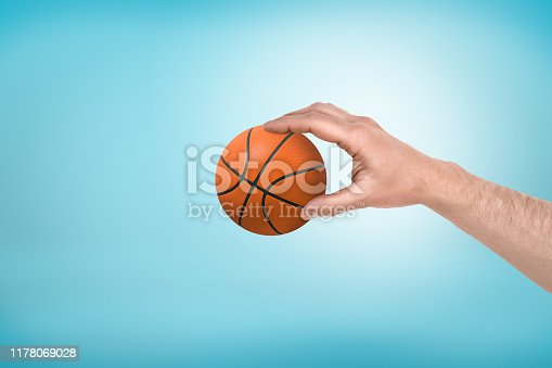 Side close-up of man's hand holding little basketball on light-blue background. Set goals. My game, my rules. Real player.