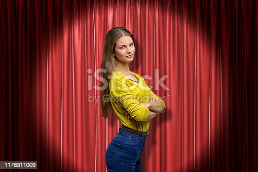 939155332 istock photo Side close-up of young woman in yellow jumper and blue jeans lit up by limelight standing with arms folded and looking at camera against red curtain. 1178311009