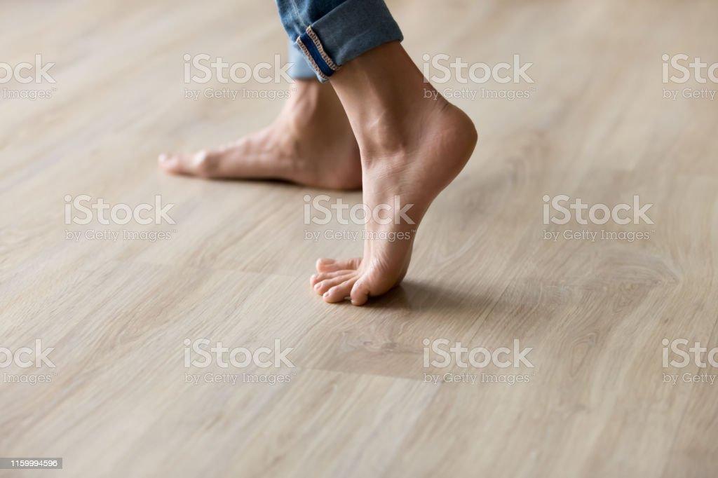 사이드 클로즈업 뷰 여성 발은 따뜻한 나무 바닥에 서 - 로열티 프리 가냘픈 스톡 사진