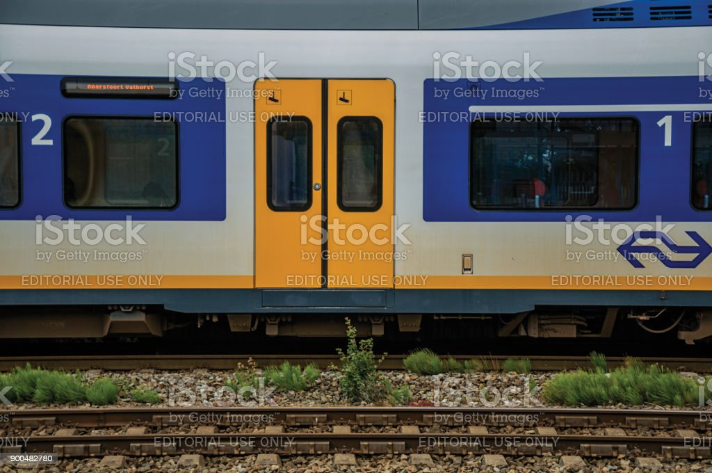 Side detail of locomotive stopped at train station platform in a sunny day at Weesp. stock photo