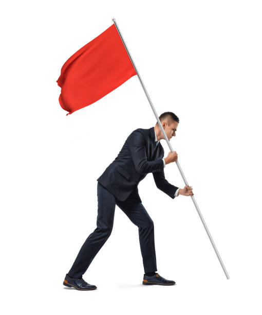 Side full length view of a young serious businessman planting a red flag on white background.