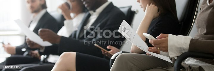 Horizontal side photo multinational applicants businesspeople sitting in queue waiting job interview holding resume papers using mobile phones, hr employment concept, banner for website header design