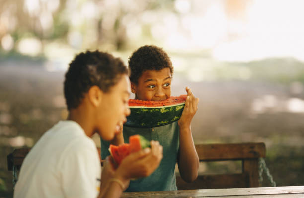 Side image of two young men are sitting and eating watermelons stock photo
