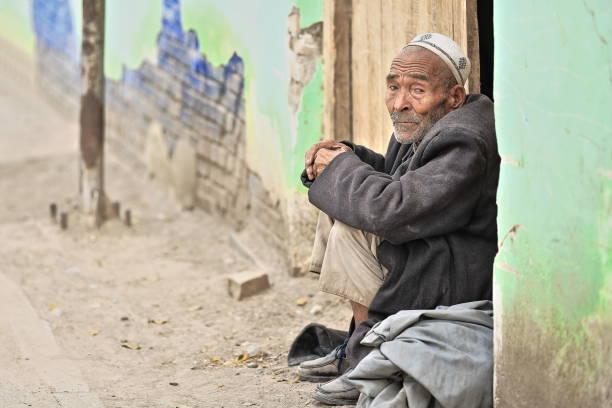 Seite aussehen uigurischen alten Mann sitzend auf einem Türsturz-Livestock Markt-Hotan-Xinjiang-China-0157 – Foto