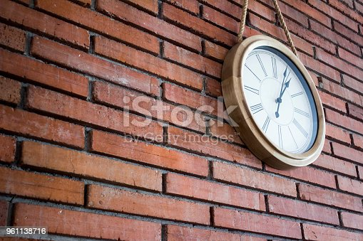 671883446istockphoto Side medium shot of a wooden wall clock with roman numerals hanging in a red brick wall. 961138716