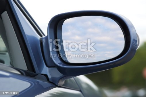 Close up of side mirror of a pearl blue luxury convertible reflecting clouds in the sky. Includes clipping path for what appears inside the mirror.