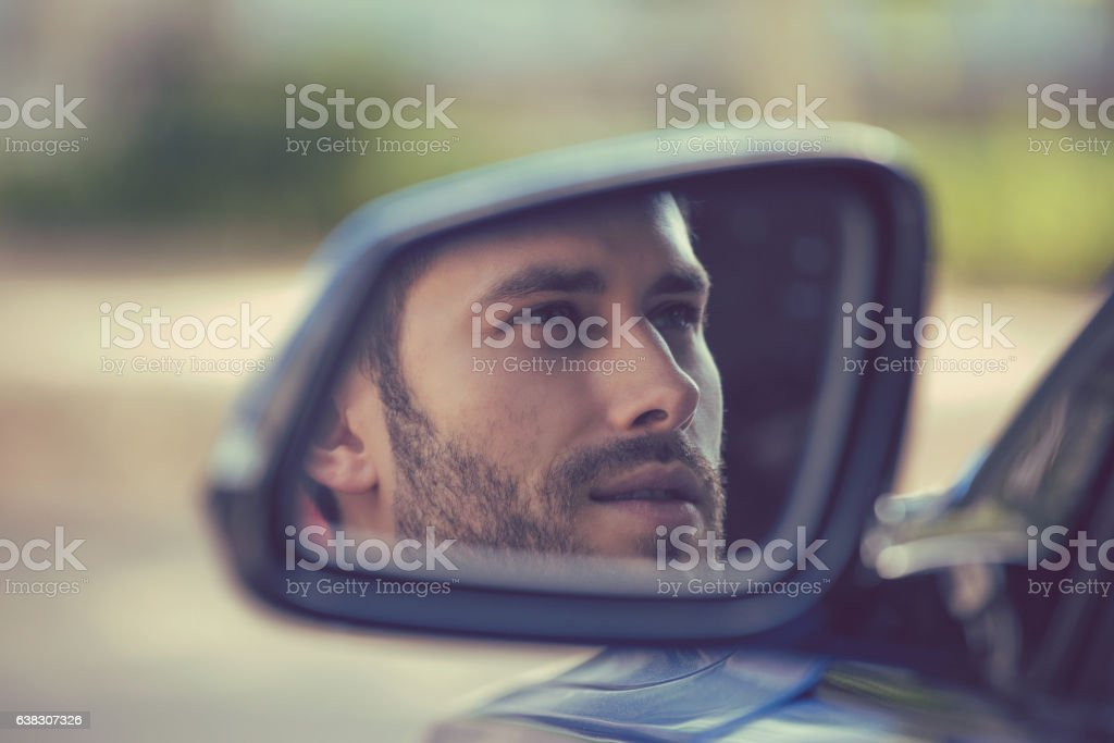 Side mirror reflection of man driving his new car stock photo
