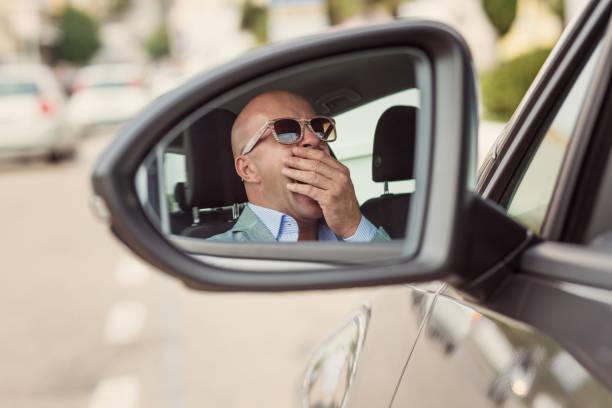 seite spiegel ansicht reflexion schläfrig müde müde gähnen erschöpft jungen mann mit sonnenbrille mit seinem auto im verkehr nach langen stunden fahrt. verkehrskonzept sleep deprivation unfall - kinder die schnell arbeiten stock-fotos und bilder