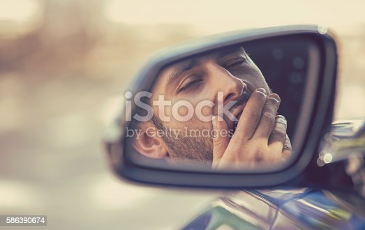 istock Side mirror view sleepy tired yawning man driving car 586390674