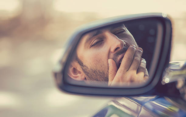 Side mirror view sleepy tired yawning man driving car stock photo