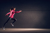 Side motion view of young sexy attractive healthy fitness sporty active slim girl with sportswear running in front of the grey wall at night on the street.