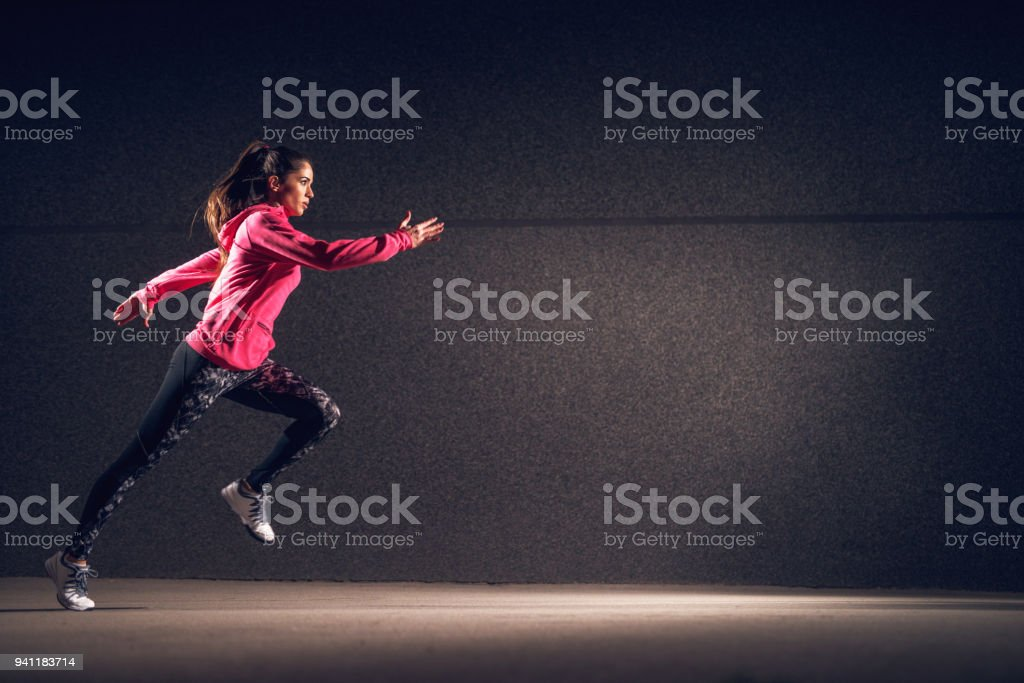Side motion view of young sexy attractive healthy fitness sporty active slim girl with sportswear running in front of the grey wall at night on the street. stock photo