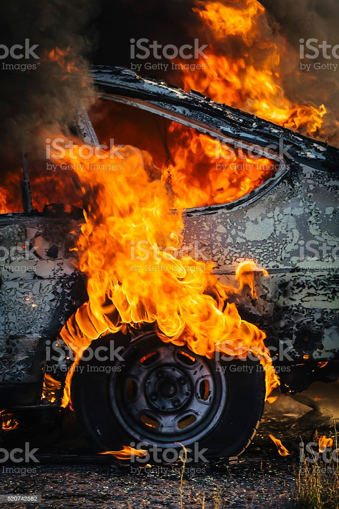 Side of a Burning car with tire covered in flames stock photo