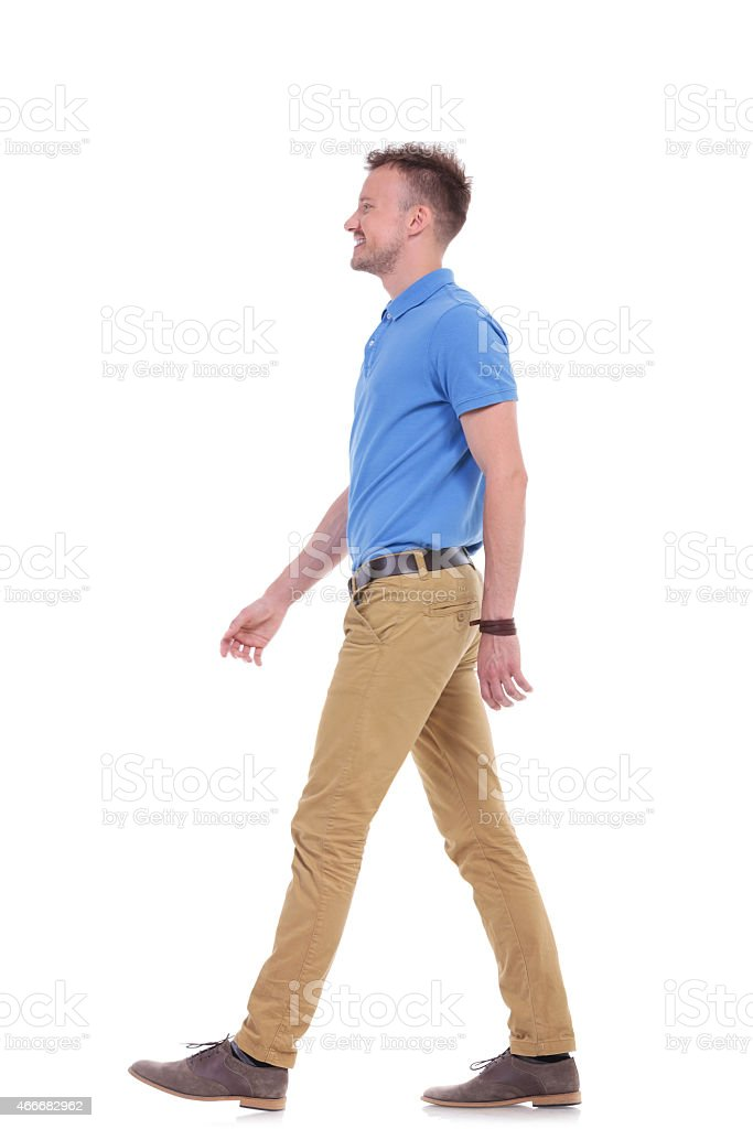 side of casual young man walking stock photo