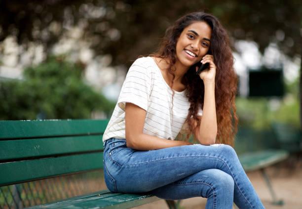 Seite der glücklichen jungen indischen Frau sitzt auf Parkbank sprechen mit Telefon – Foto