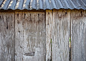 Side of old wood shed with tin roof. Rustic and weathered wood planks with rusty nails.