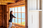 Side of one, lonely, alone young woman standing by large glass window looking at peaceful ocean view, cliff, in rustic wooden house