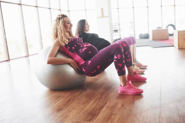 Seitenfoto von zwei schwangeren Frauen, die mit Hilfe von Stabilitätsbällen Fitness-Übungen machen – Foto