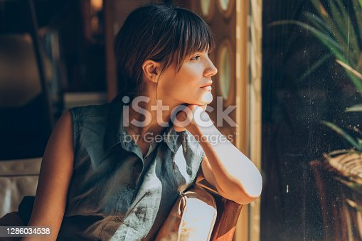 Young pretty woman, causally dressed, relaxing at her favorite coffee place