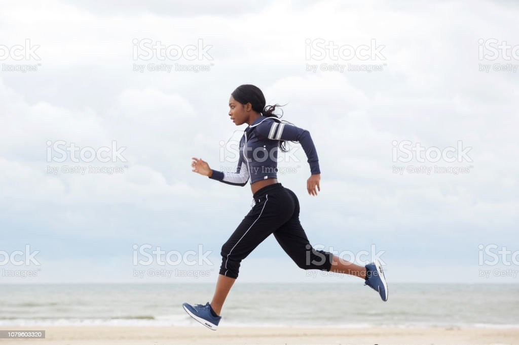 retrato do lado do americano africano mulher correndo na praia foto de stock royalty-free