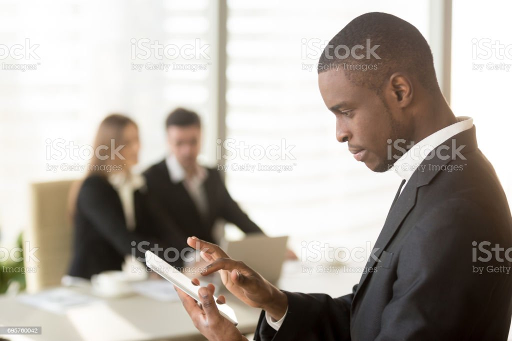 Side portrait of afro american businessman holding smartphone or tablet stock photo