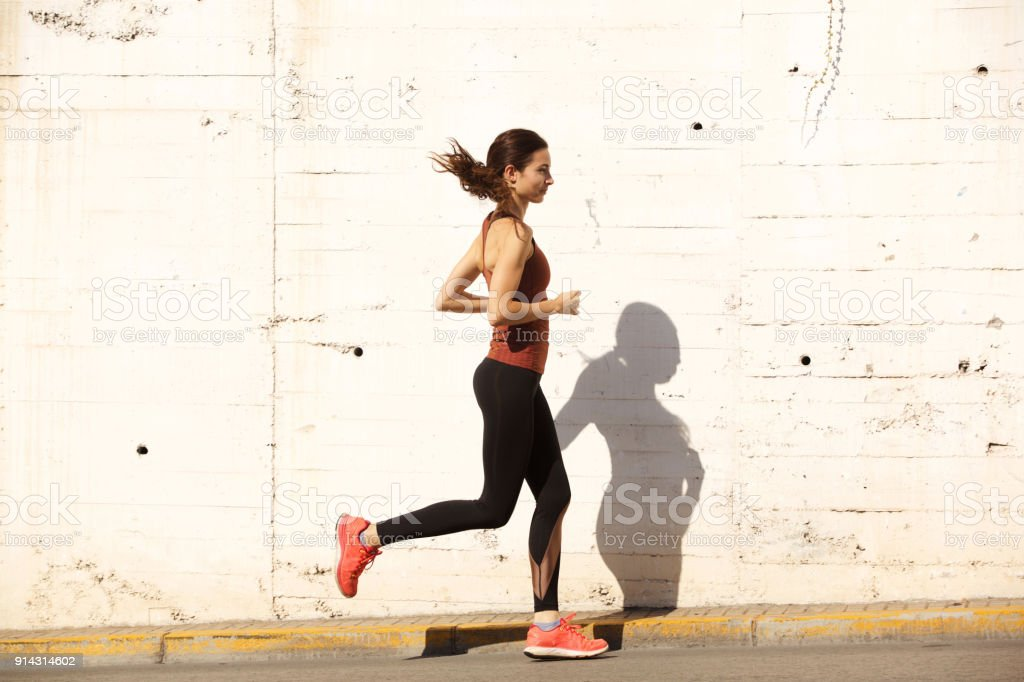 Side portrait of fit young woman running outdoors royalty-free stock photo
