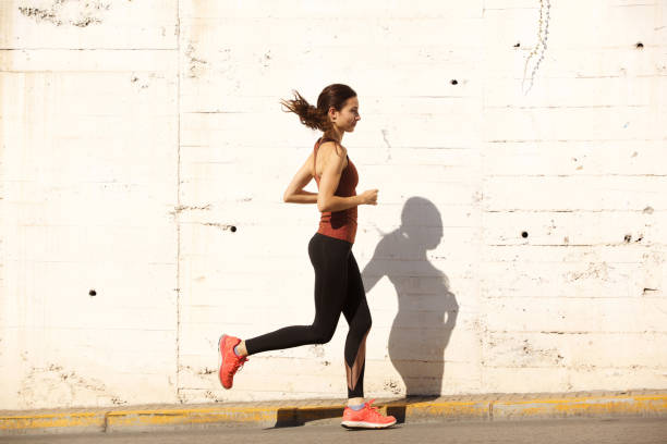 side portrait of fit young woman running outdoors - young woman running city imagens e fotografias de stock