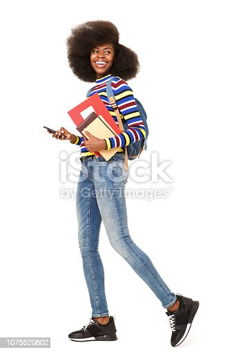 Full body side portrait of happy young black woman walking with cellphone and book bag