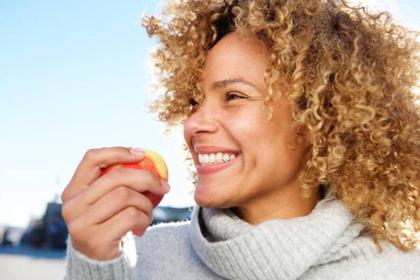 Seitenporträt von gesunden jungen afrikanischen Amerikanerinnen mit Apfel – Foto
