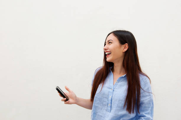 Side portrait of laughing woman with long hair holding mobile phone stock photo