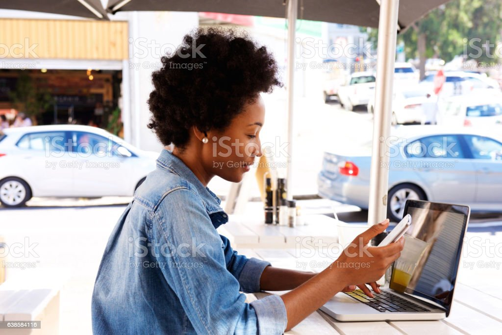 Side portrait of woman using cellphone with laptop stock photo