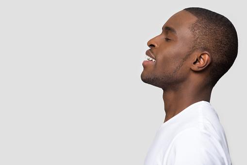 Side profile african man face closed eyes enjoy fresh air